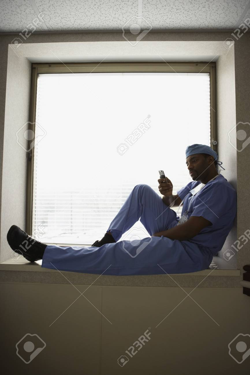 African male surgeon sitting in window alcove Stock Photo - 16090524