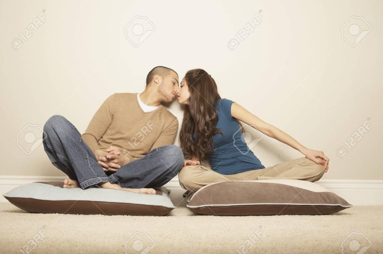 Young Hispanic Couple Sitting On Floor Pillows Kissing, San Rafael ...