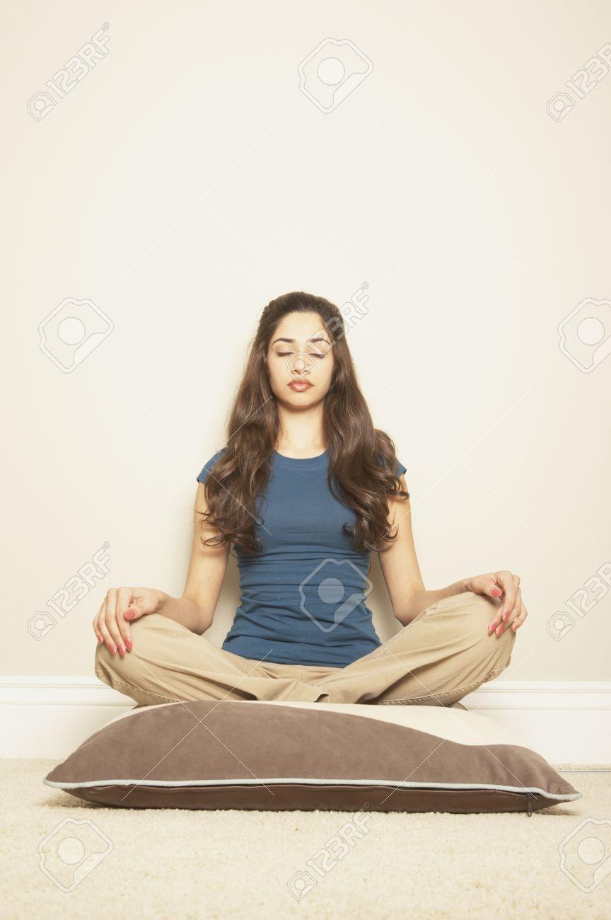 Young Hispanic Woman Sitting Cross-legged On A Floor Pillow,.. Stock ...