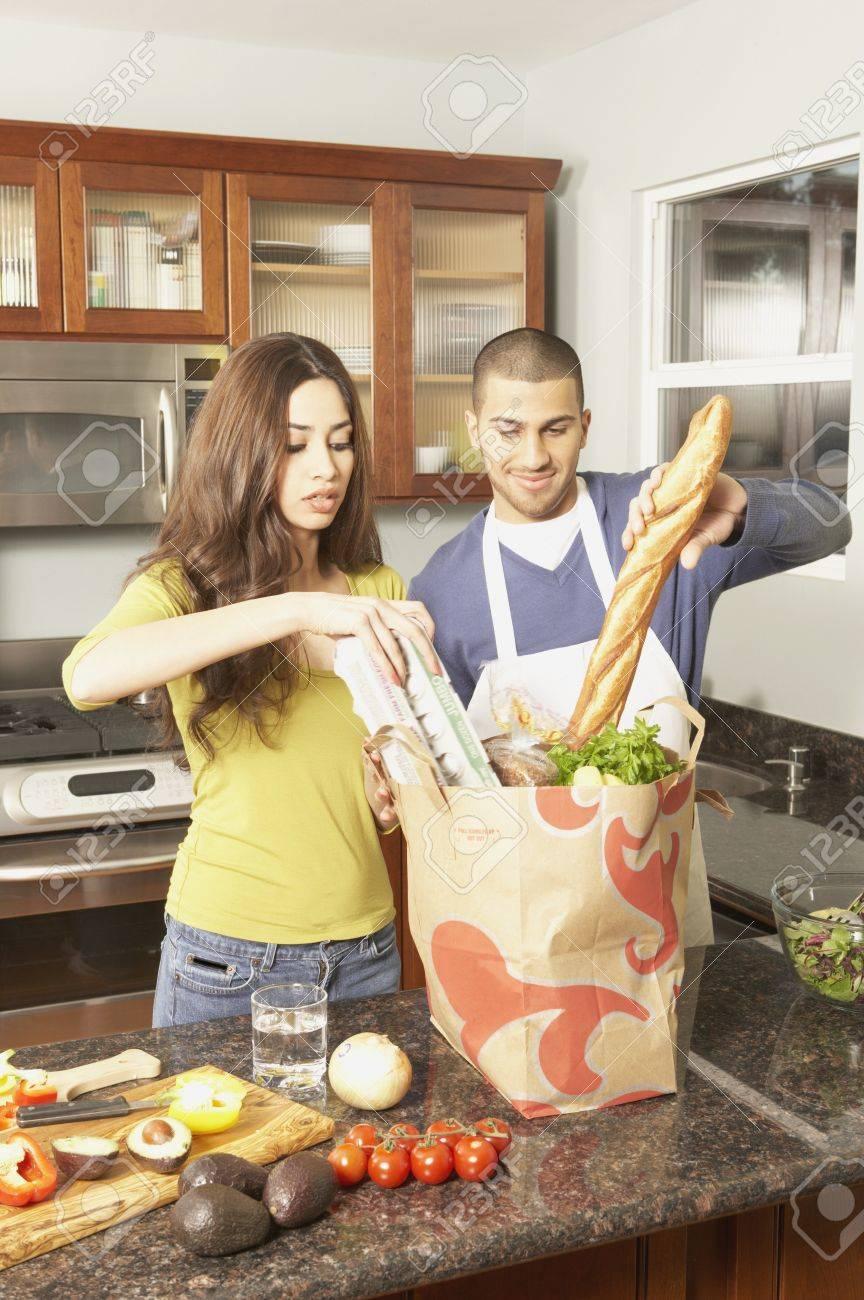 Young Hispanic couple unpacking grocery bag, San Rafael, California, United States Stock Photo - 16070340