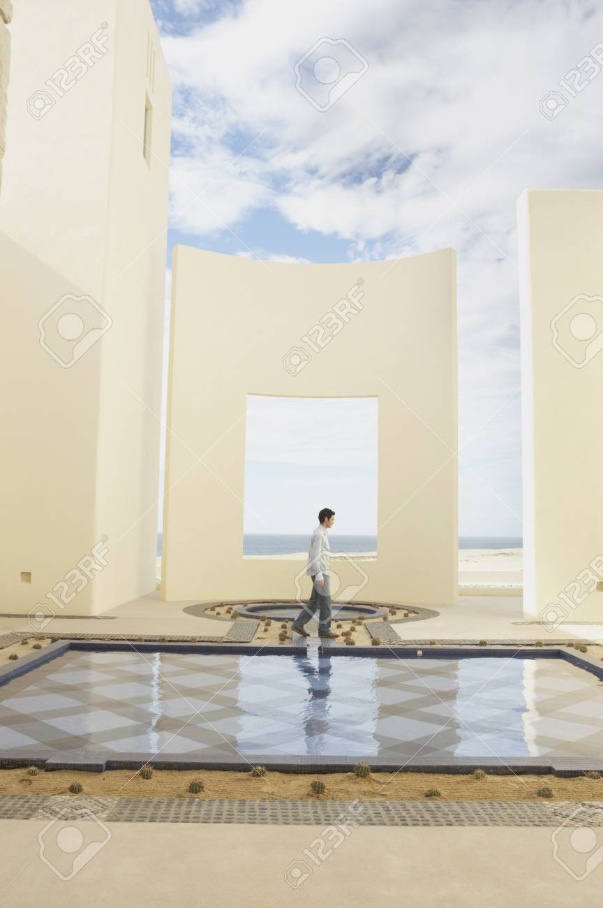 Man walking past luxury hotel pool, Los Cabos, Mexico Stock Photo - 16070359