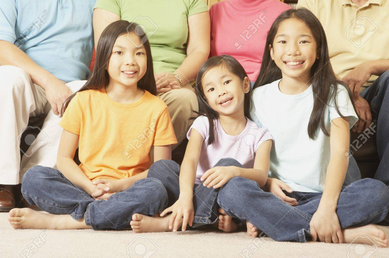 Three young Asian sisters sitting cross-legged on the floor, San Rafael, California, United States Stock Photo - 16090893