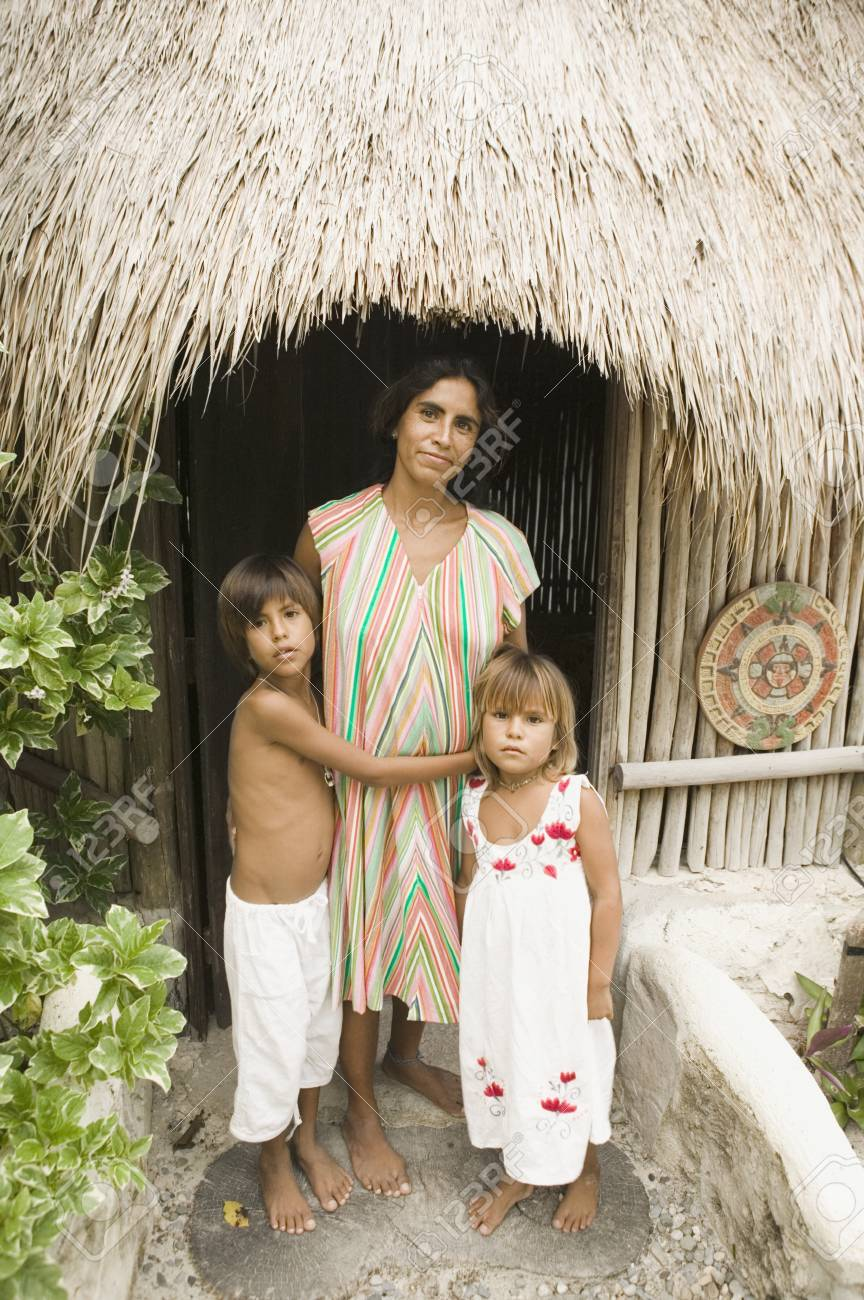 Mother posing with her children outside a straw hut Stock Photo - 16091165