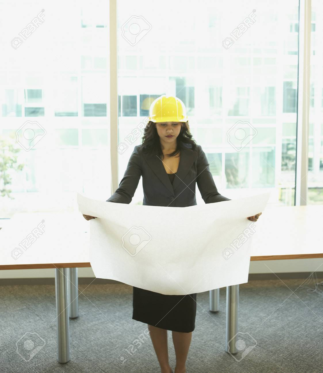 Businesswoman wearing hard had and looking at blueprints Stock Photo - 16091567
