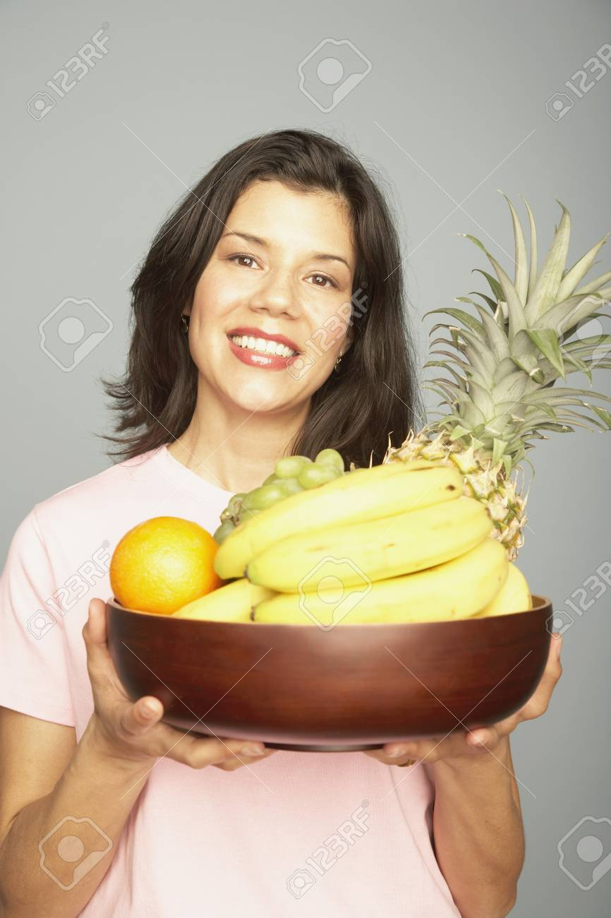Studio shot of woman holding bowl of fruit Stock Photo - 16091658