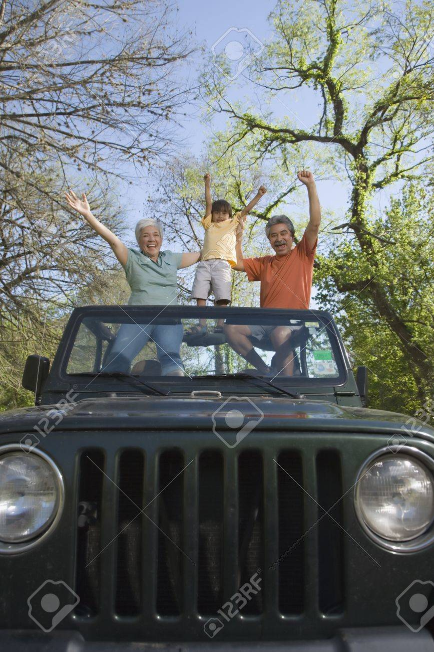 Grandparents and grandson standing in jeep with arms raised Stock Photo - 16091841