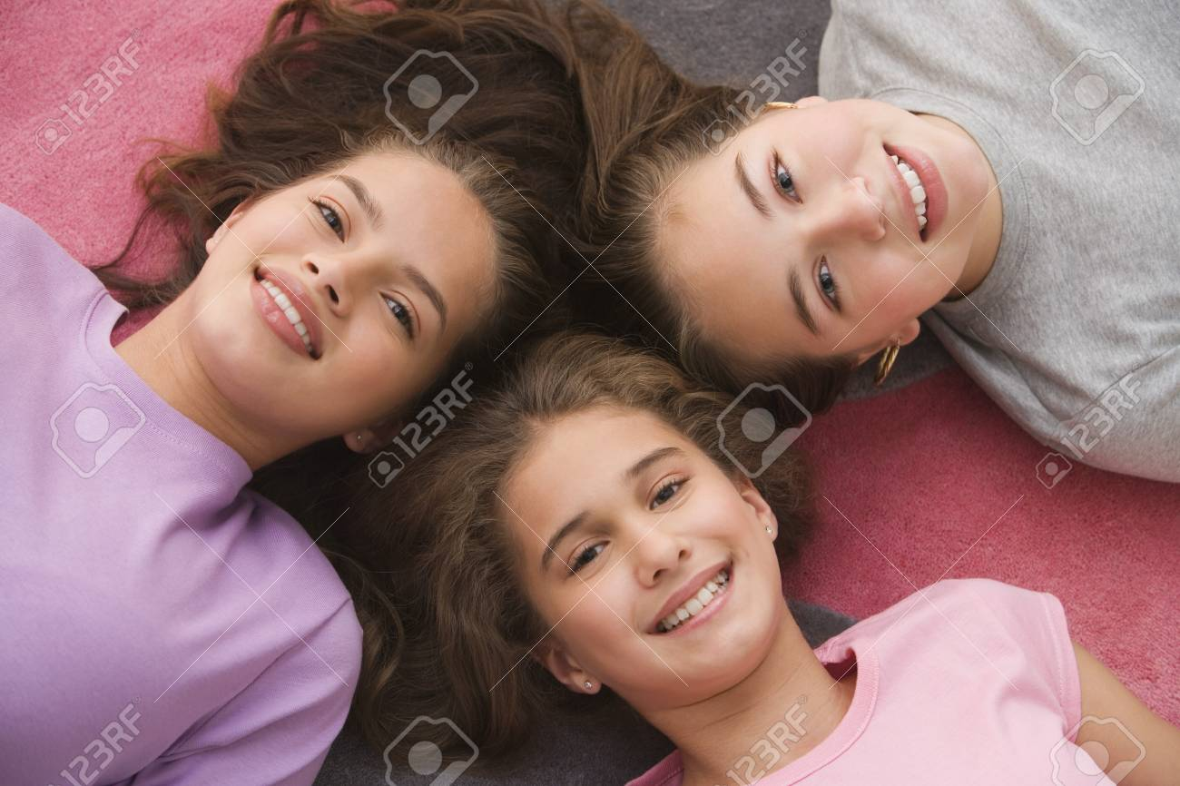 High angle view of Hispanic sisters laying on floor Stock Photo - 16091907