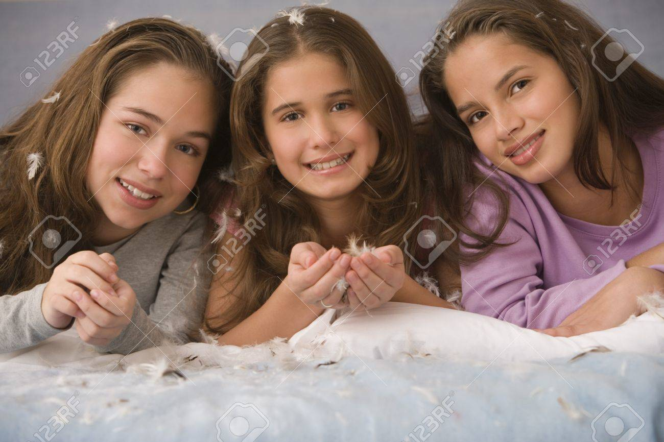 Hispanic sisters laying on bed with down feathers Stock Photo - 16091908