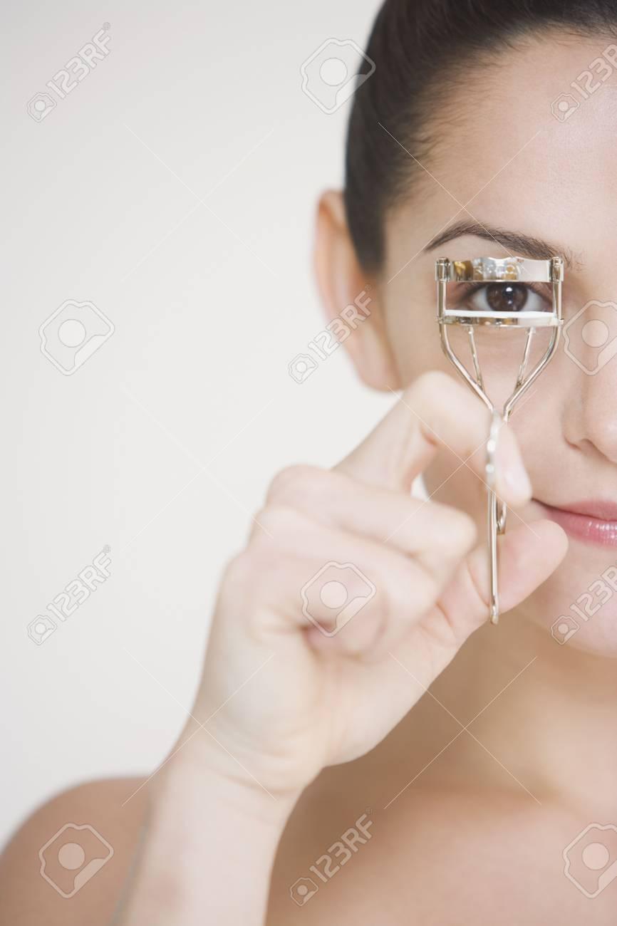 Close up studio shot of woman using eyelash curler Stock Photo - 16091910