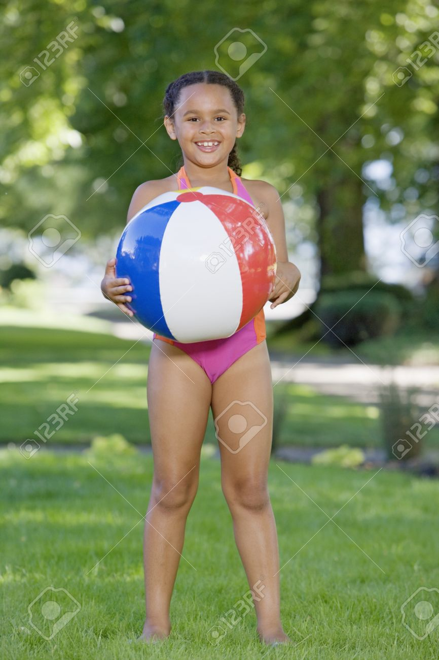 youngster girls Stock Photo - Young African girl wearing bathing suit and holding ball outdoors
