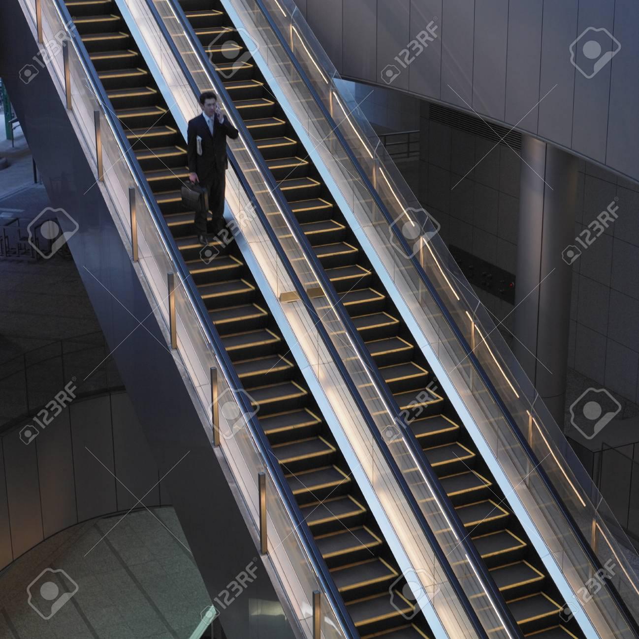 Businessman with briefcase on escalator Stock Photo - 16092061