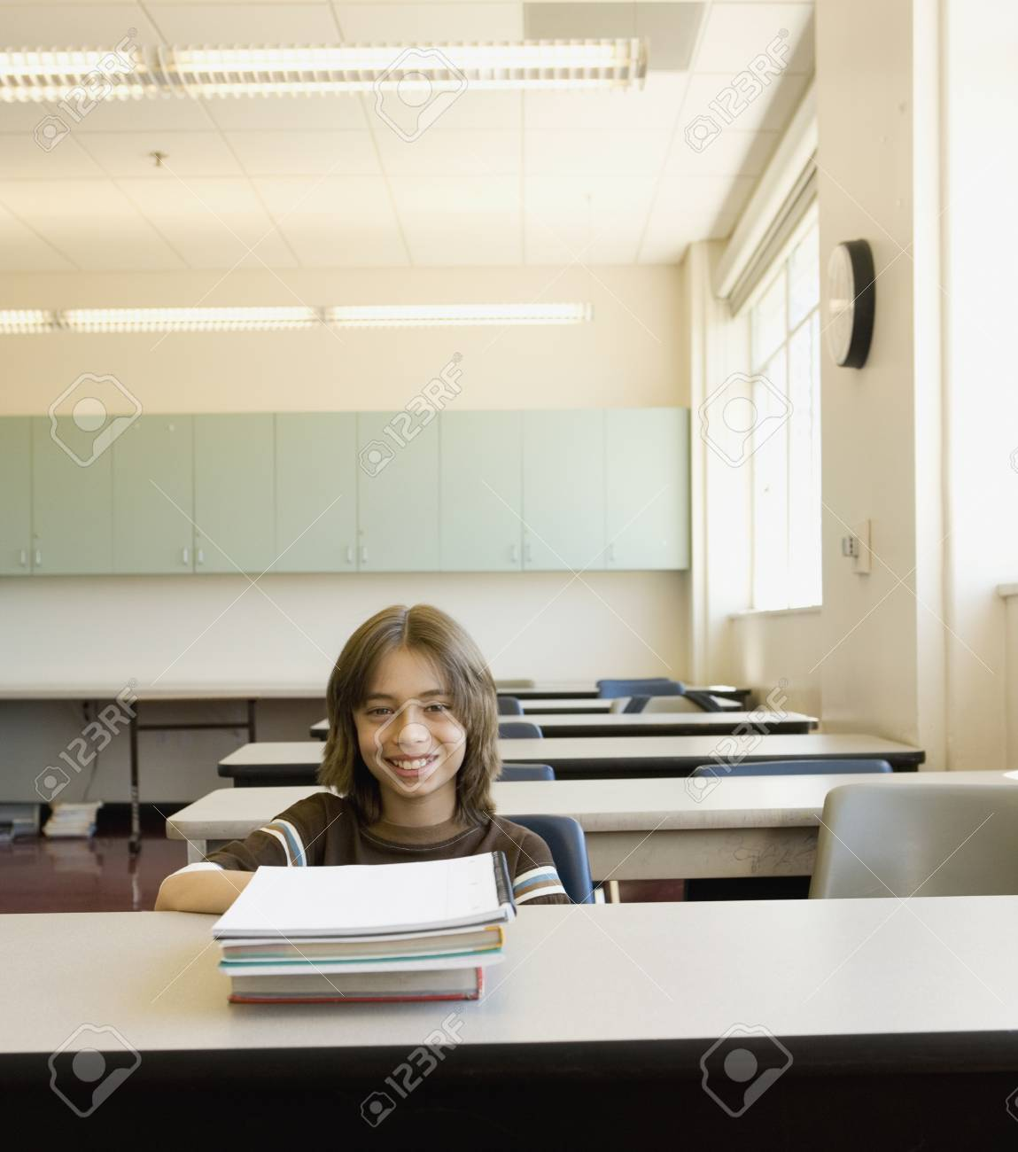 Boy sitting at desk in empty classroom Stock Photo - 16092231