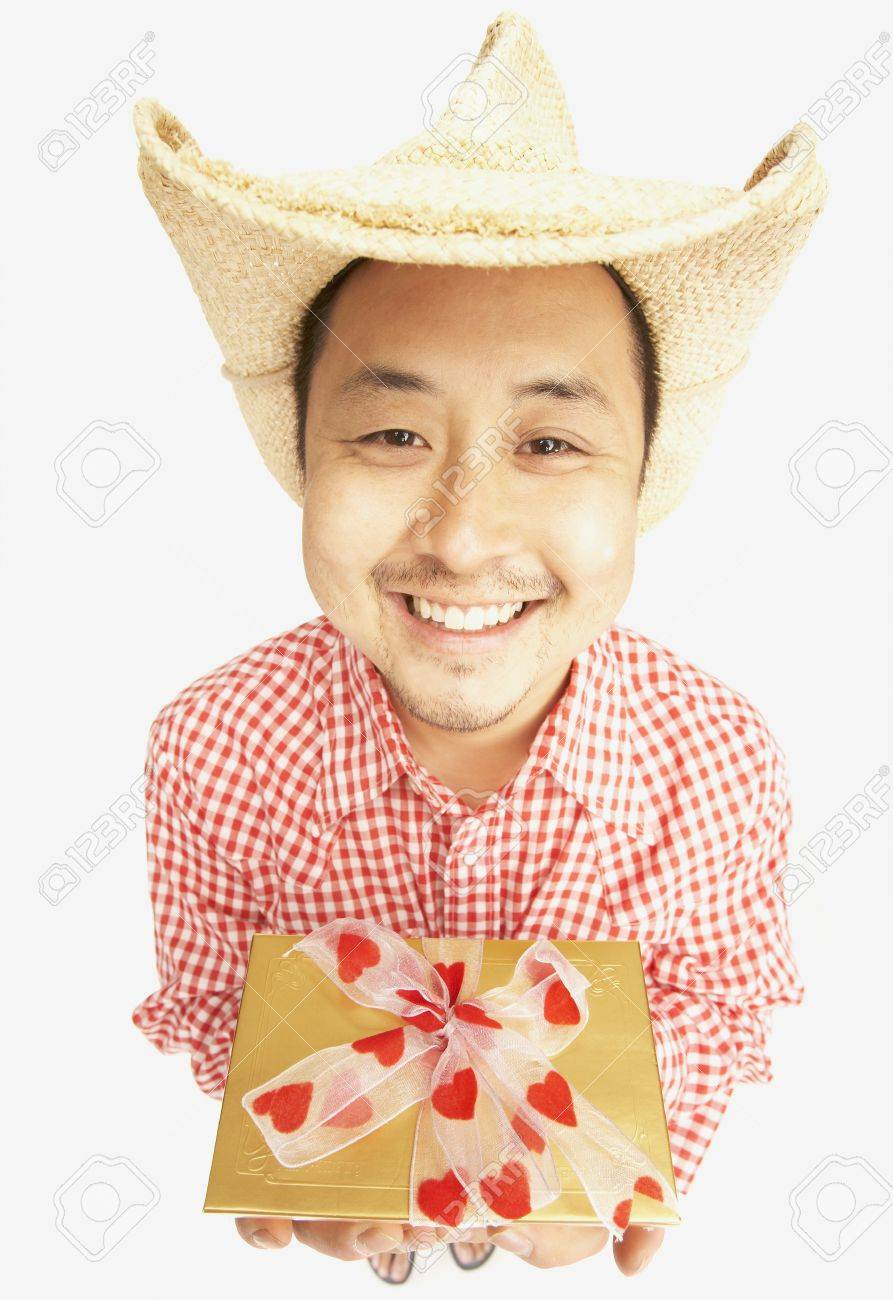 Asian man wearing cowboy hat and holding gift Stock Photo - 16092581