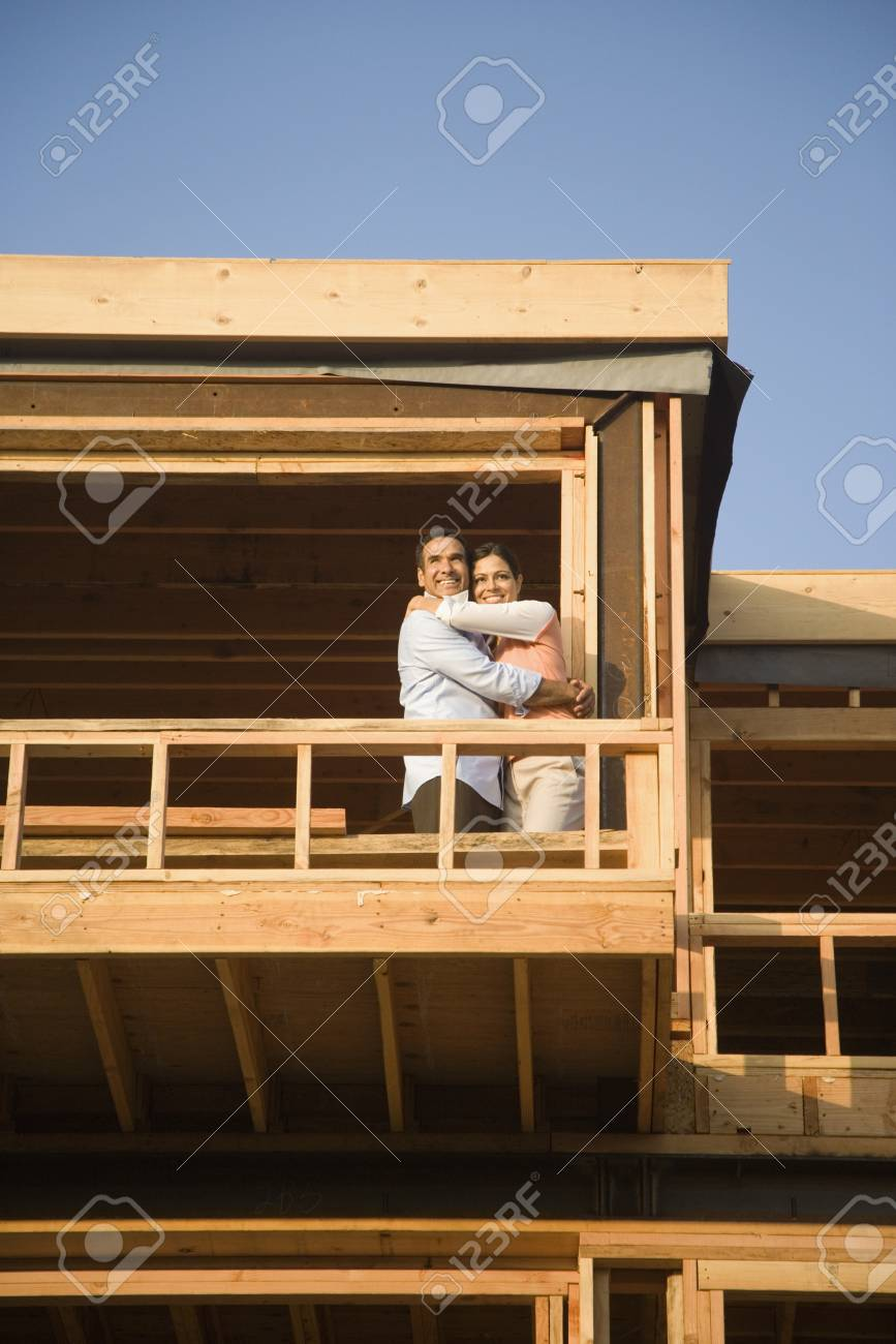 Hispanic couple hugging on balcony at construction site Stock Photo - 16092707