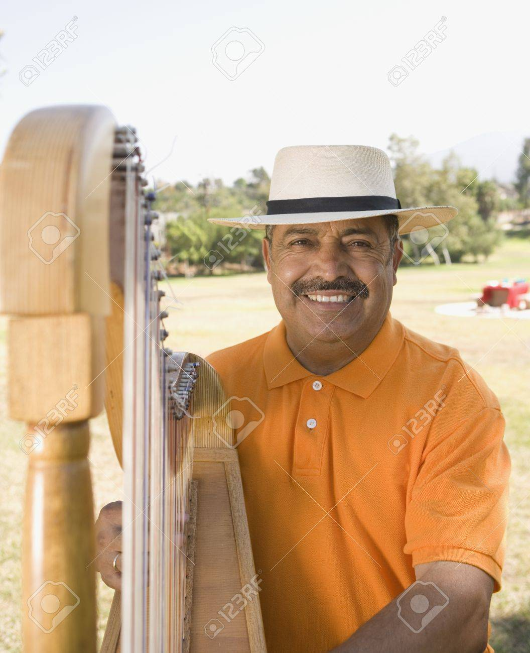 Middle-aged Hispanic man playing harp outdoors Stock Photo - 16092745
