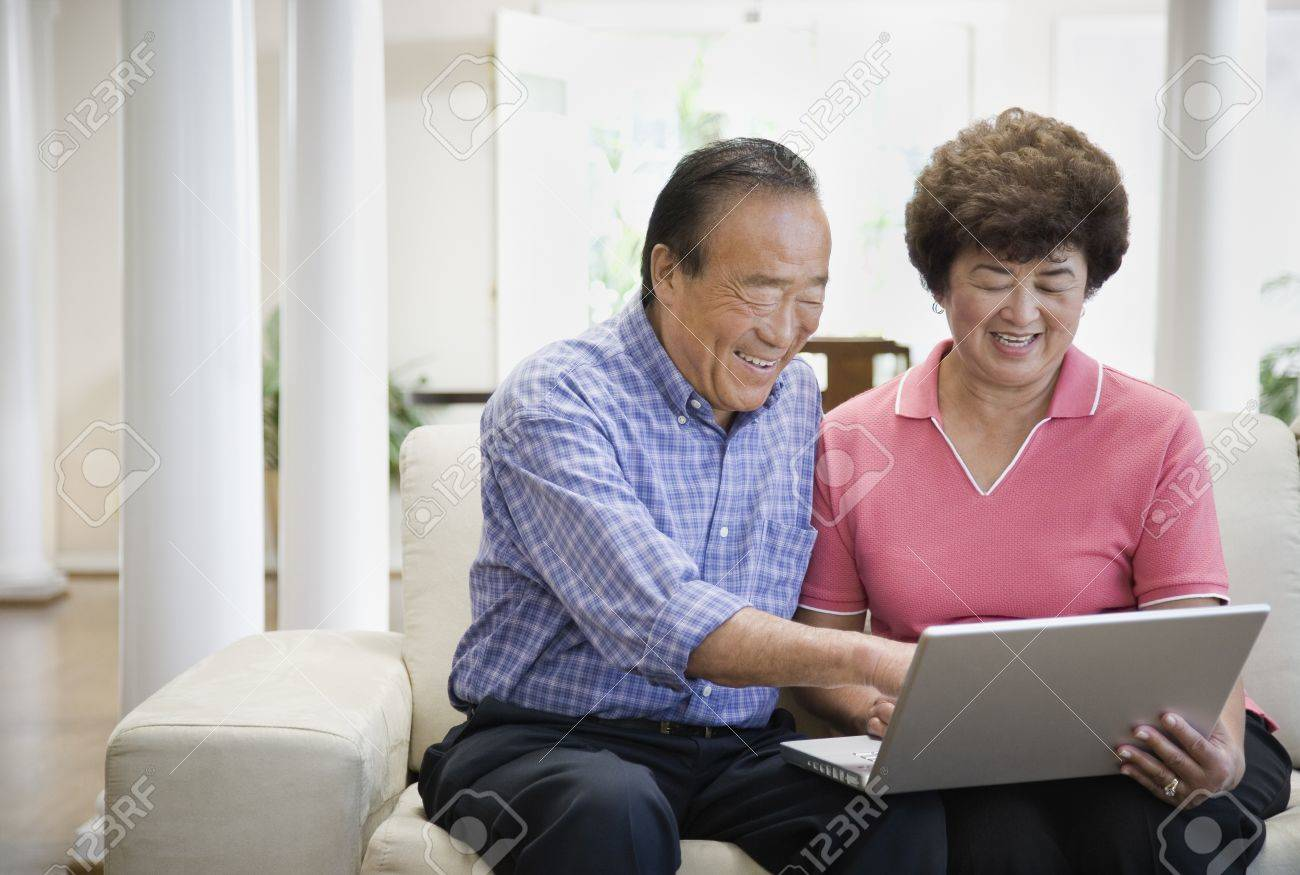 Senior Asian couple looking at laptop Stock Photo - 16092889