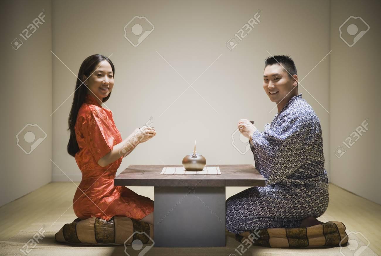 Asian couple kneeling having tea Stock Photo - 16093053