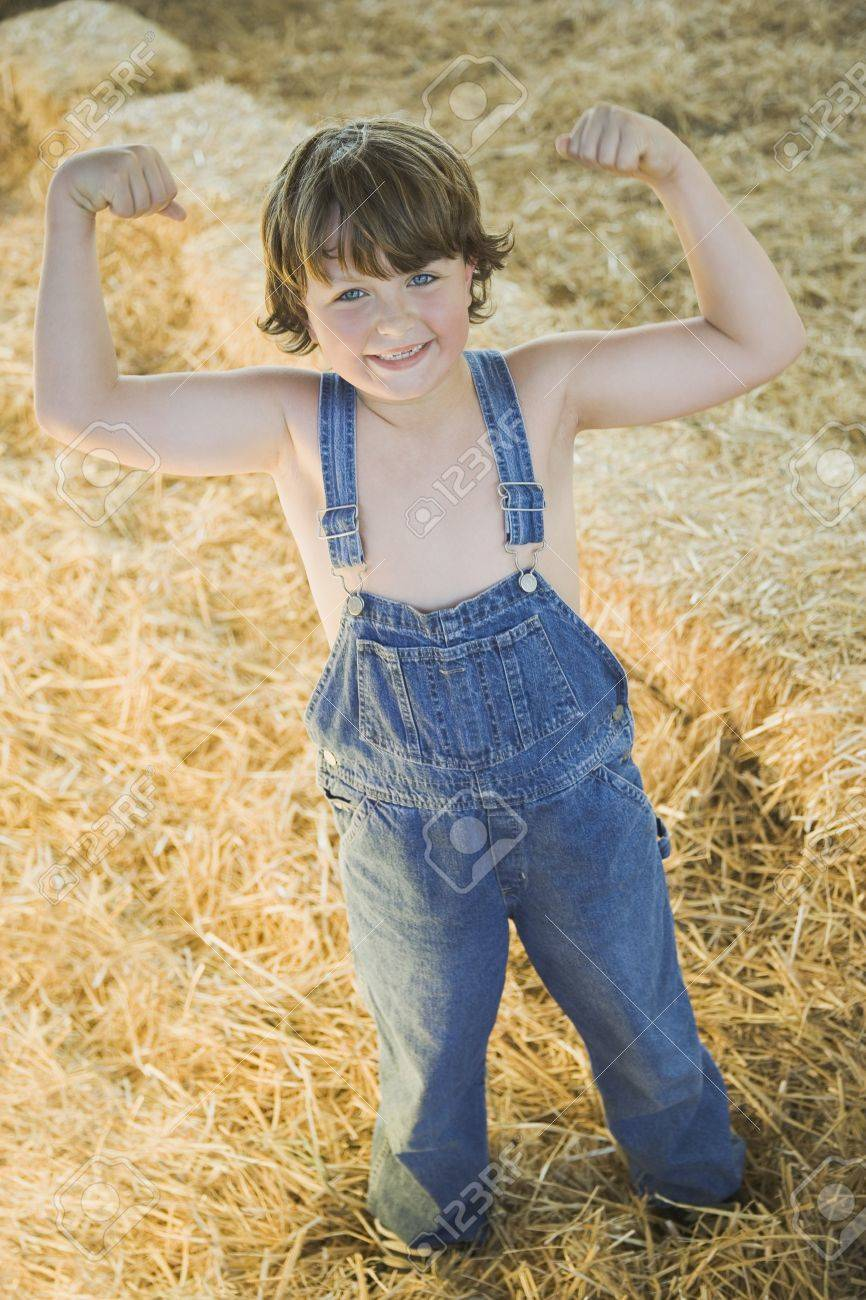 Young boy wearing overalls and flexing muscles in hay Stock Photo - 16093081