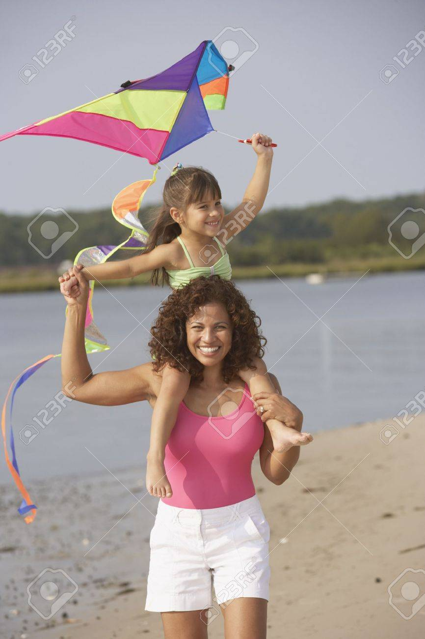 Hispanic mother and daughter flying kite on beach Stock Photo - 16093102