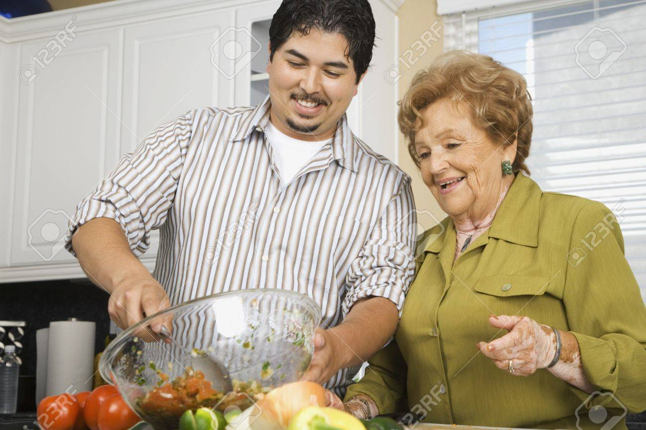 Hispanic Mother And Adult Son Preparing Food In Kitchen Stock Photo ...