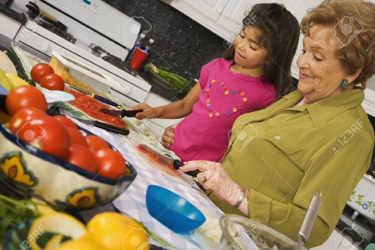 Hispanic grandmother and granddaughter preparing food in kitchen Stock Photo - 16093187