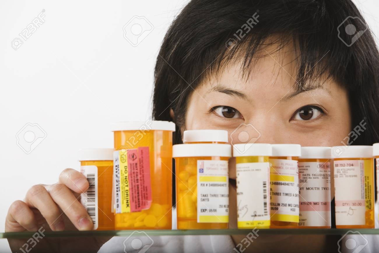Asian woman looking over bottles of medication Stock Photo - 16093570