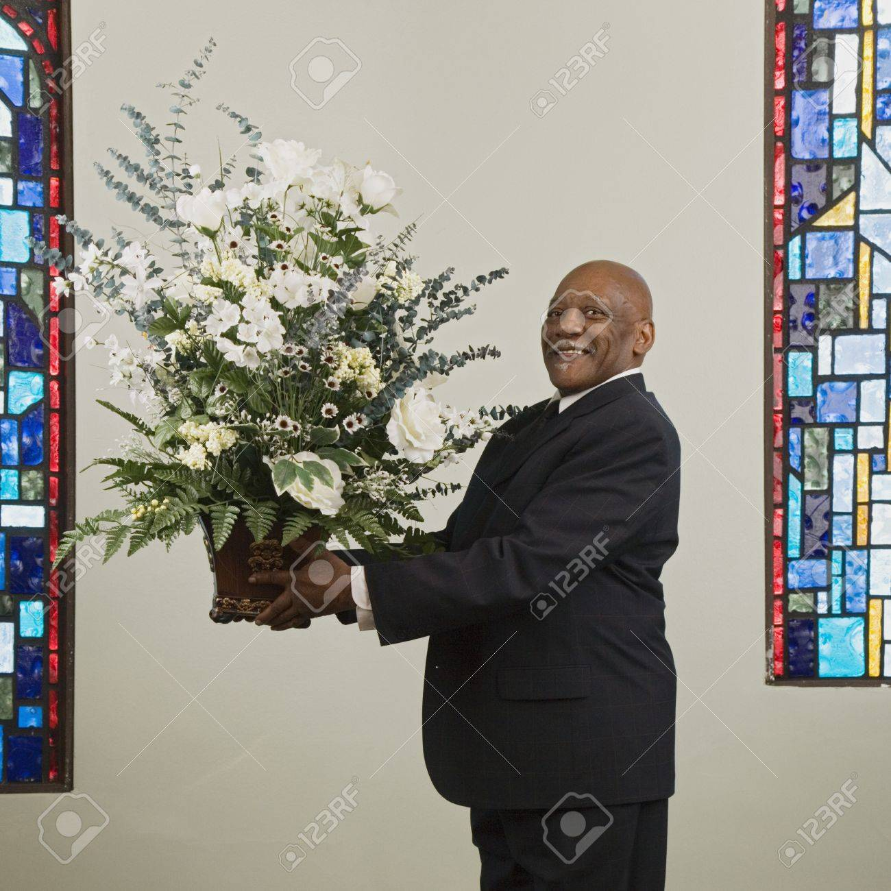 African man holding flower bouquet in church Stock Photo - 16094667