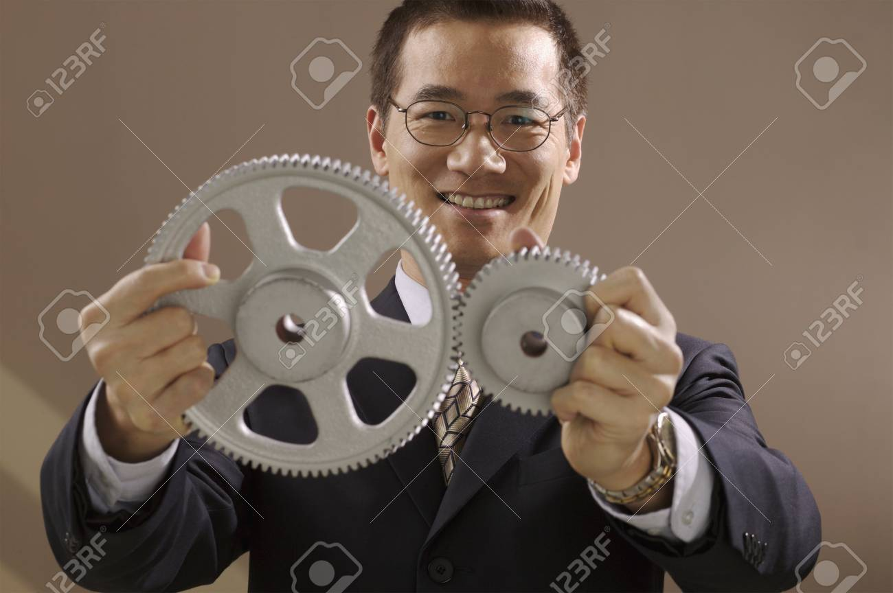 Asian businessman holding gear wheels Stock Photo - 16094822