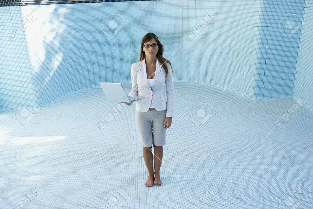South American businesswoman in empty swimming pool Stock Photo - 16095175