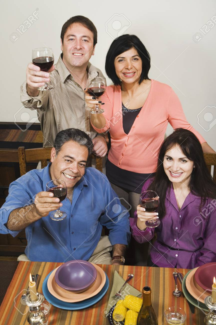 Two middle-aged toasting at dinner table Stock Photo - 16096087