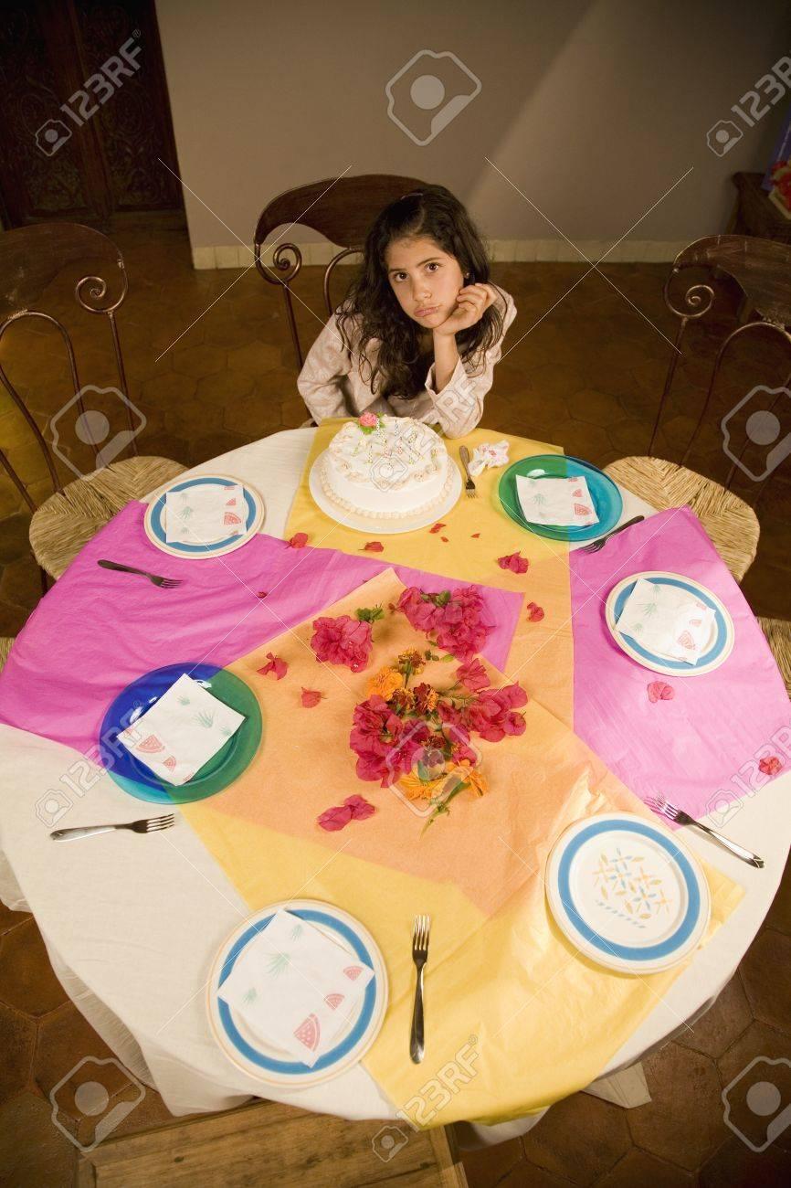 Hispanic girl sitting alone at birthday party Stock Photo - 16096181