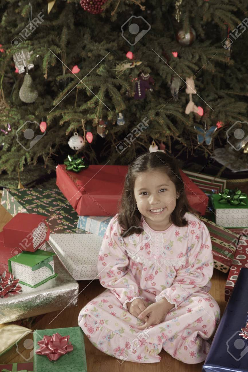 Hispanic girl surrounded by Christmas gifts Stock Photo - 16096253