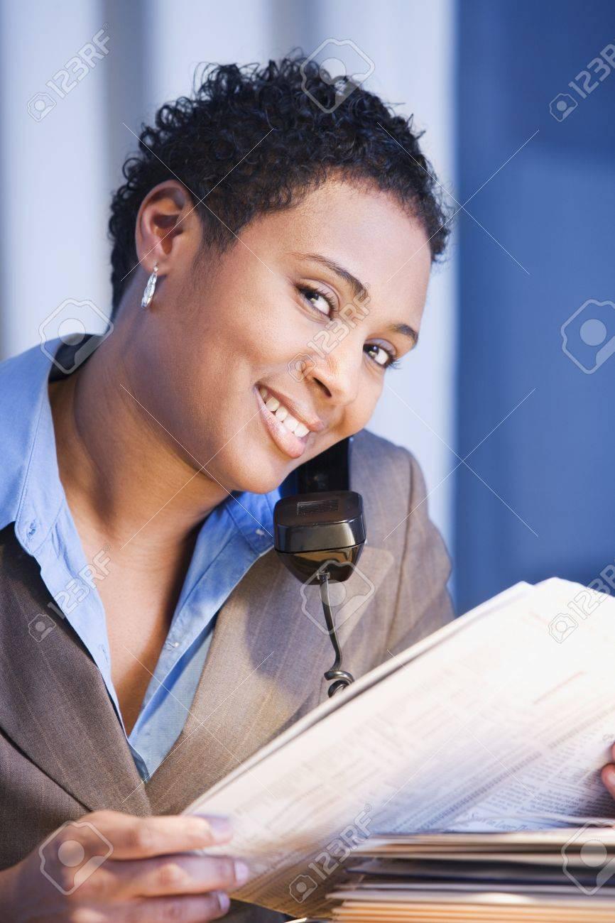 African businesswoman reading newspaper Stock Photo - 16096276