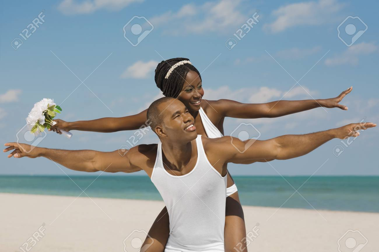 African Bride And Groom With Arms Outstretched At Beach Stock Photo ...