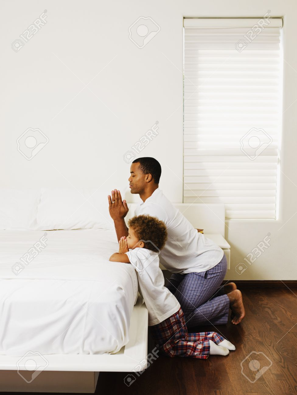 African Father And Son Praying At Bedside Stock Photo   35788220