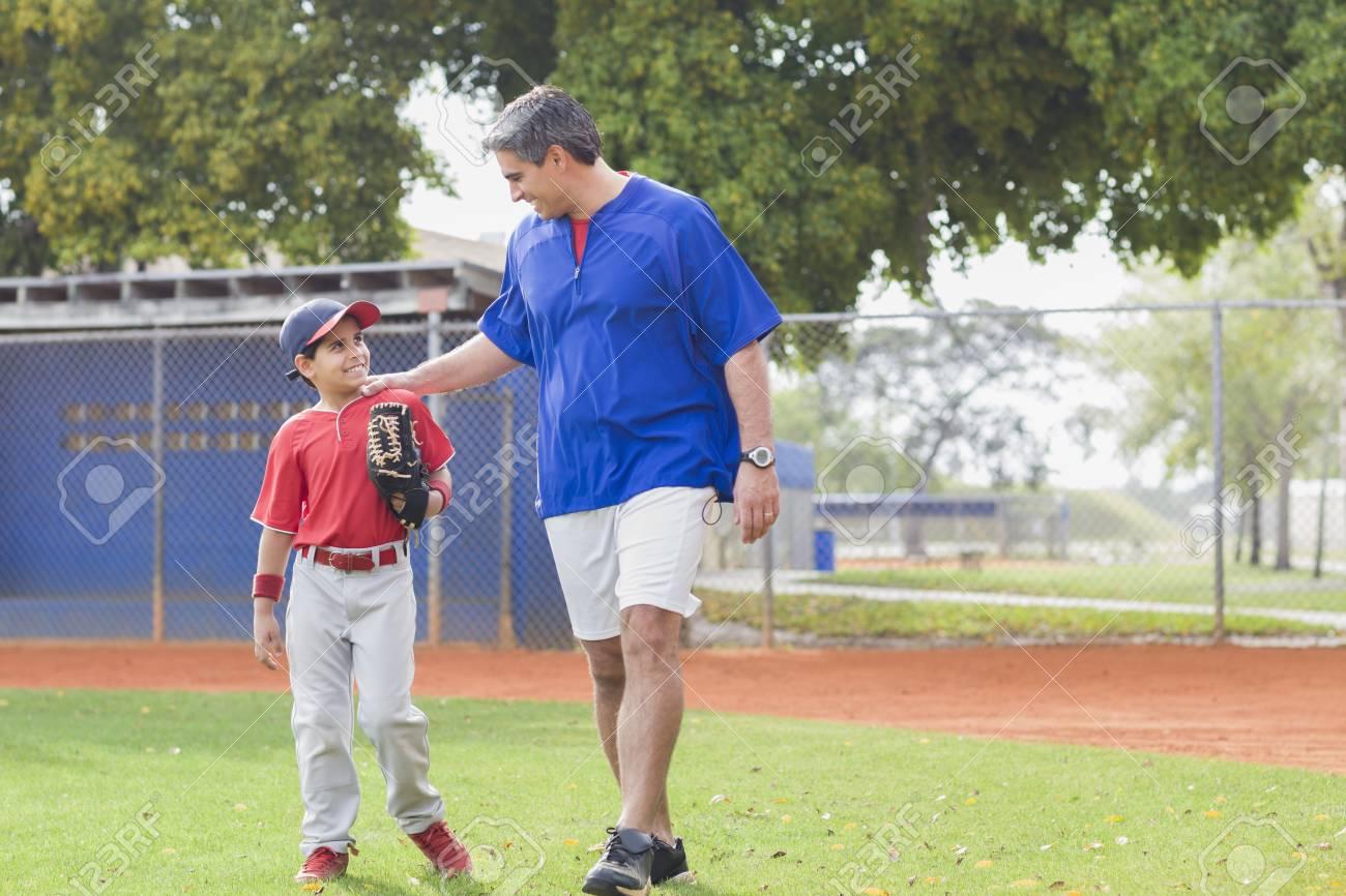 Hispanic coach and young baseball player - 107929105