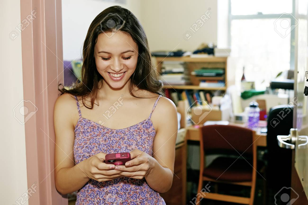 Mixed race college student using cell phone in dorm - 107914122