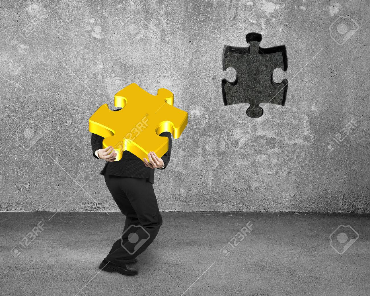 Businessman Carrying 3D Gold Jigsaw Puzzle Piece To Insert The Dark Hole On  Concrete Wall Background