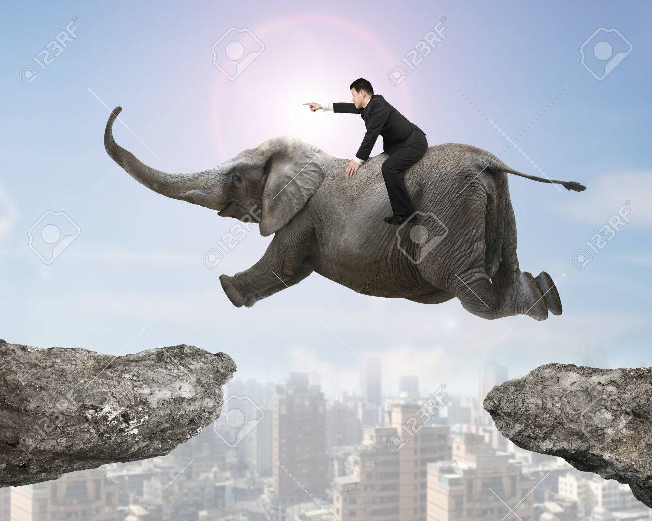 Man with pointing finger gesture riding elephant flying over two cliffs, with sunny sky cityscape background. - 50341600