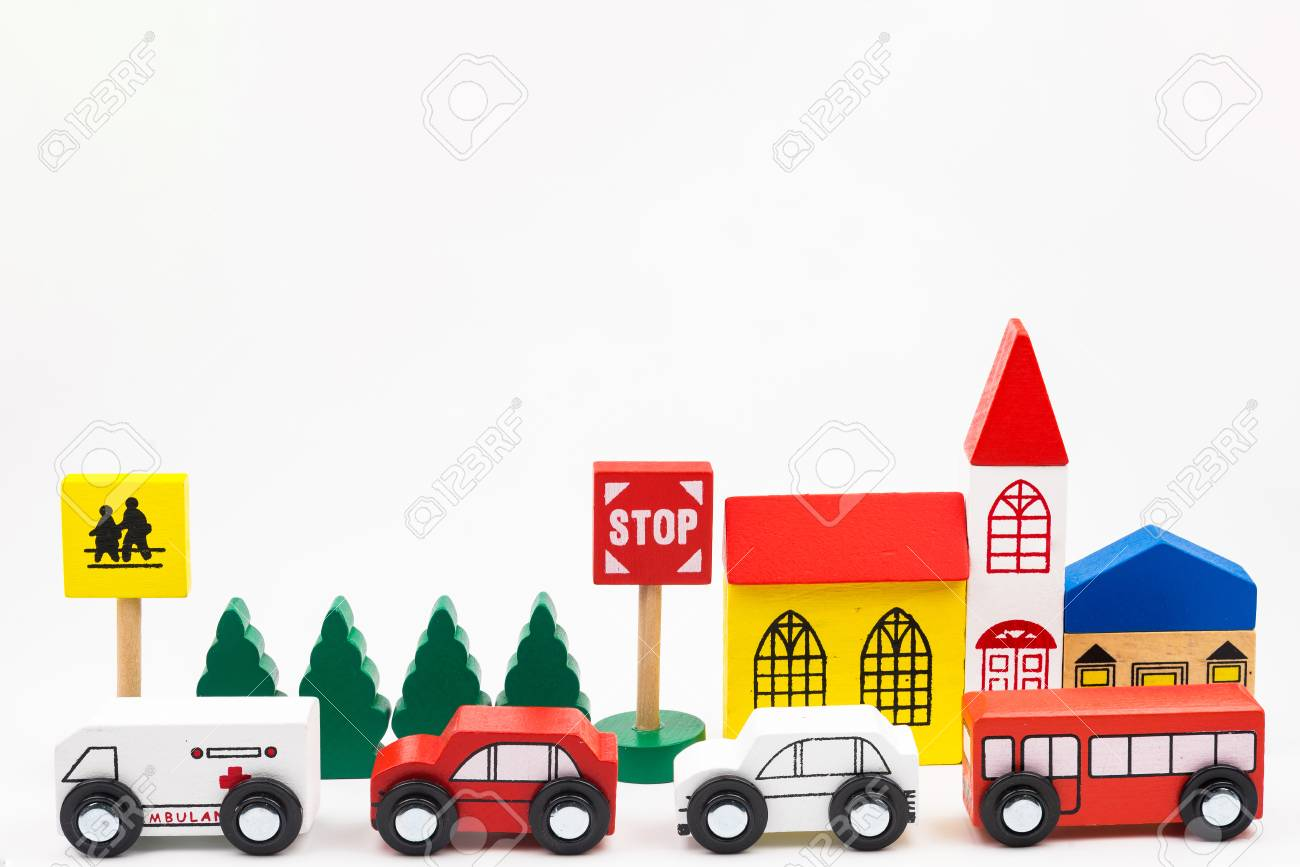 Road traffic with wooden toy cars in the town on white background,