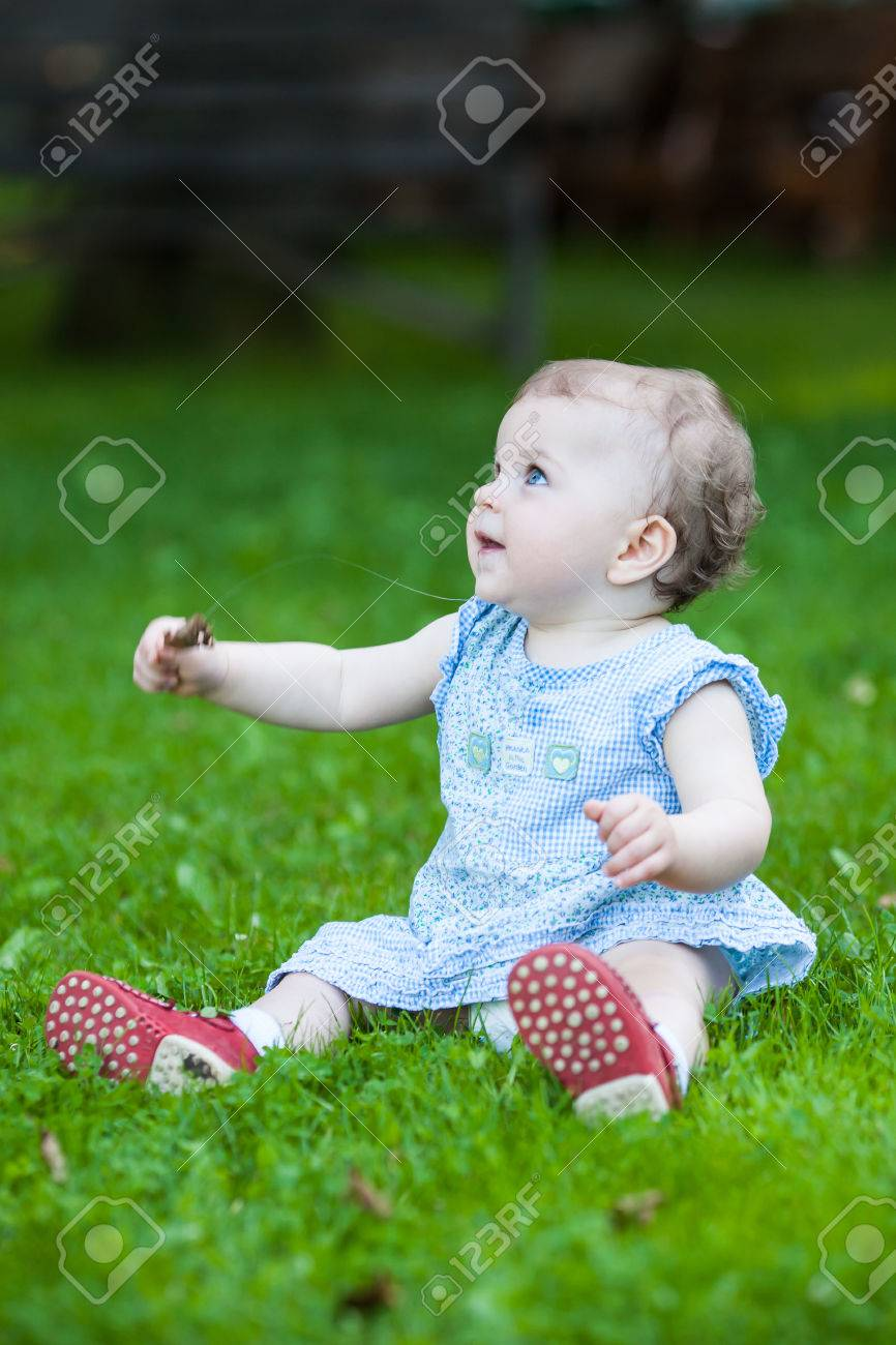 dbaa63eb8 beautiful drooling cute baby girl in a blue dress sitting on the grass  Stock Photo -