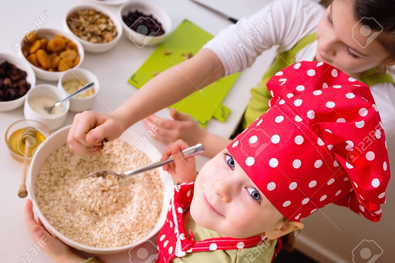 Marvelous Foto De Archivo   Hermanas Felices Cocinar Juntos. Los Niños Pequeños De La  Familia Niños Felices Divirtiéndose Preparar Granola En La Cocina En El  Hogar
