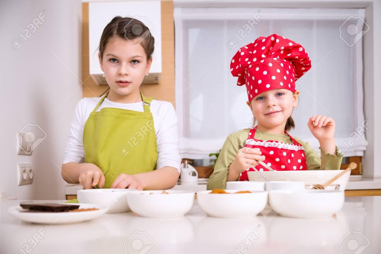 Foto De Archivo   Hermanas Felices Cocinar Juntos. Los Niños Pequeños De La  Familia Niños Felices Divirtiéndose Preparar Granola En La Cocina En El  Hogar