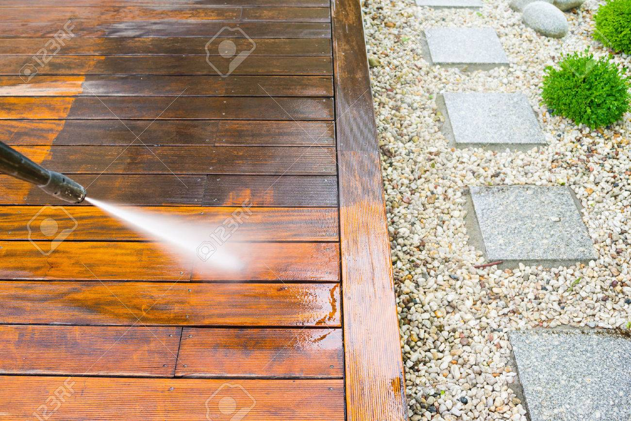 cleaning terrace with a power washer - high water pressure cleaner on wooden terrace surface - 69081084