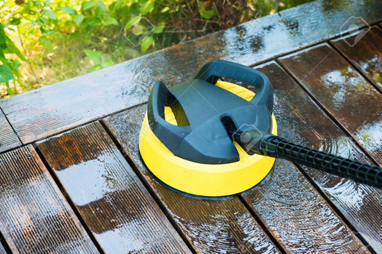 Terraza De Limpieza Con Una Arandela De La Energía Limpiador De Alta Presión De Agua En La Superficie De Terraza De Madera