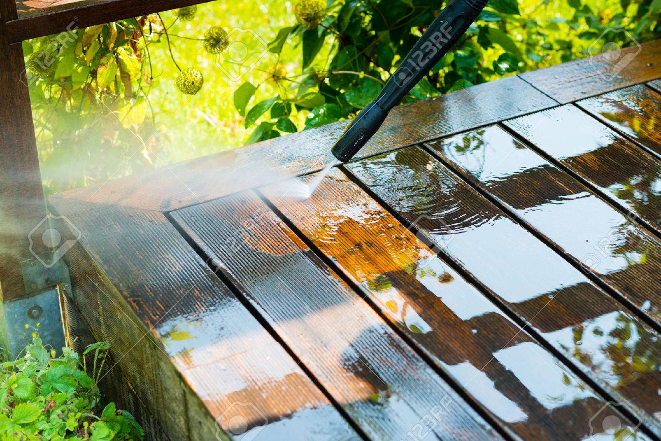 cleaning terrace with a power washer - high water pressure cleaner on wooden terrace surface - 69081315