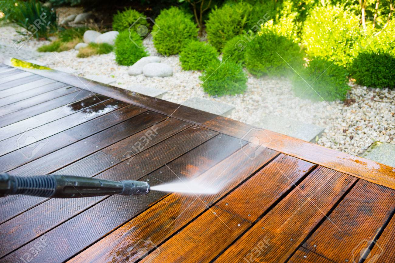 cleaning terrace with a power washer - high water pressure cleaner on wooden terrace surface - 69120438