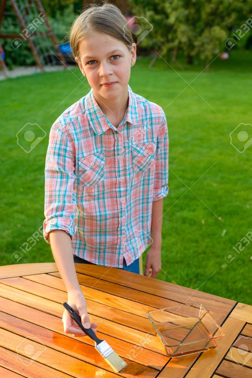 Jolie Jeune Fille Tenant Une Brosse à Appliquer Une Peinture De Vernis Sur Une Table De Jardin En Bois Peinture Et Dentretien Du Bois Huile Cire