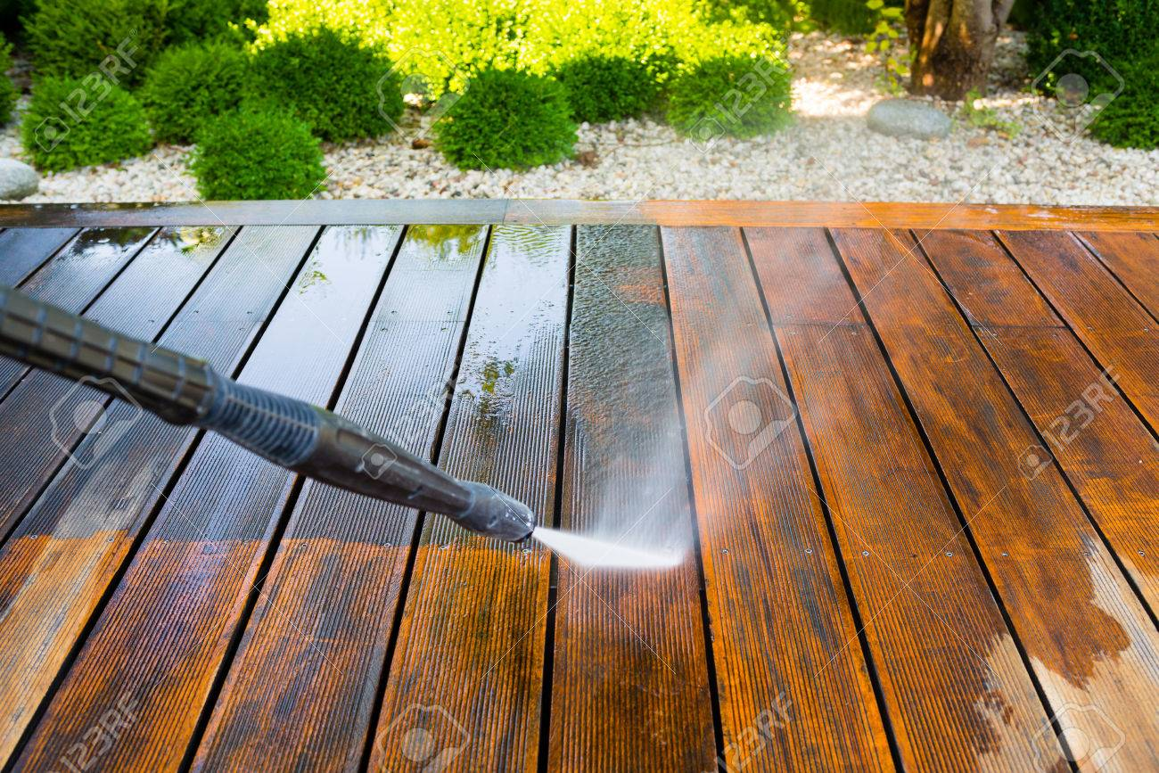 Cleaning Terrace With A Power Washer   High Water Pressure Cleaner On Wooden  Terrace Surface Stock
