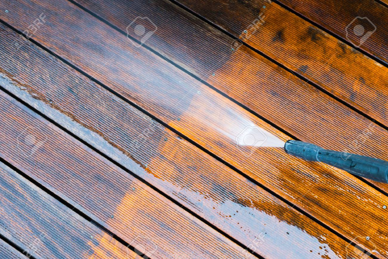 cleaning terrace with a power washer - high water pressure cleaner on wooden terrace surface - 69051695